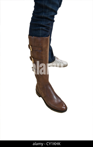 A female person trying on a brown boot isoltaed on a white background - Stock Photo