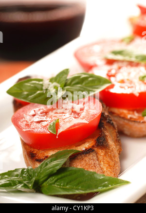 Delicious Bruschetta with tomato and basil on a white place with a glass of wine in the background. - Stock Photo