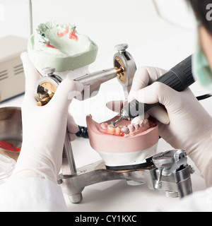 Dental technician working with articulator in dental laboratory  - Stock Photo
