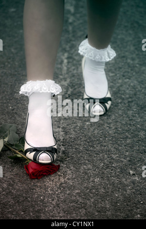 feet of a woman are stepping on a red rose - Stock Photo