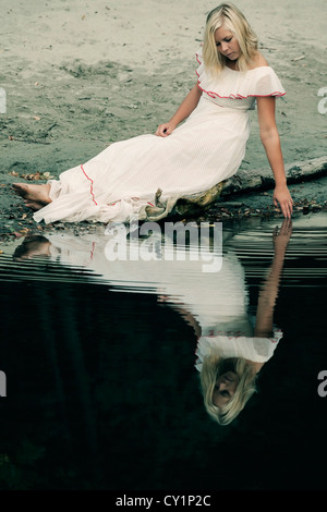 a woman in a white dress is sitting on a trunk near a pond and playing with her fingers in the water - Stock Photo