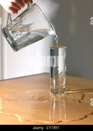 Water Being Poured From A Jug Into A Glass And Its Overflowing - Stock Photo