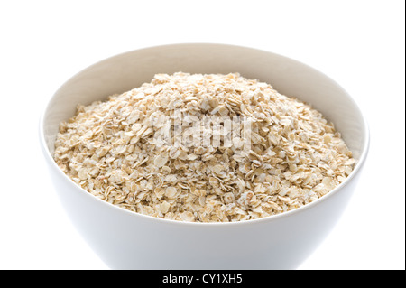 porridge oats dry uncooked in a white bowl - Stock Photo