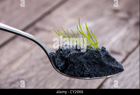 Caviar and Dill on a Spoon against wooden background - Stock Photo