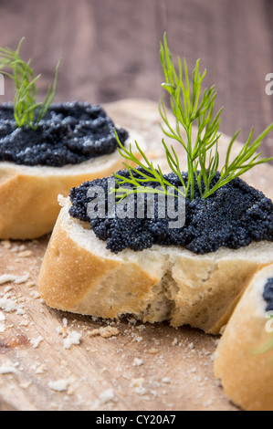 Some Caviar on fresh Baguette against wooden background - Stock Photo