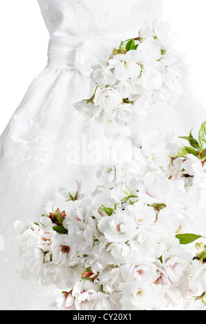 White on white floral arrangement with gown in background - Stock Photo