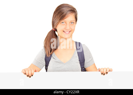 School girl with backpack posing behind white panel isolated on white background - Stock Photo