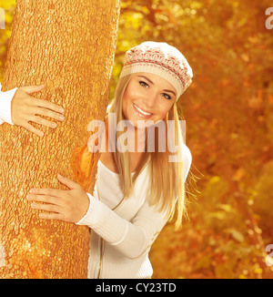 Photo of cute happy girl in autumnal park, closeup portrait of sweet blonde woman wearing stylish beret, attractive - Stock Photo