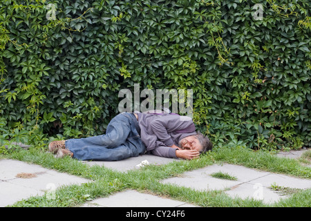 A Drunk asleep on the streets of Prague with A cut face - Stock Photo