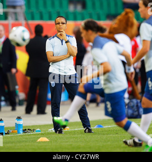 England coach Hope Powell watches her squad warm up before a 2011 FIFA Women's World Cup Group B match against Mexico. - Stock Photo