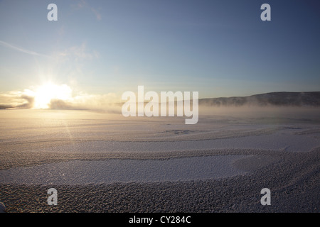 Clouds of steam rise over a freezing river on a very cold winter day in Sweden.