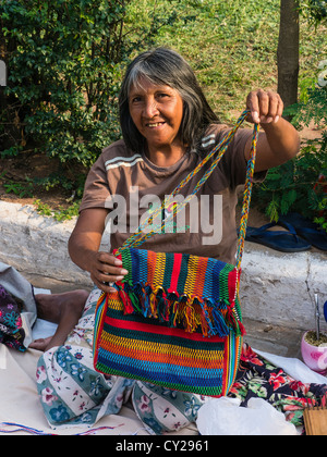 An indigenous woman sells her weavings and handicrafts on the street in Asunción, Paraguay. - Stock Photo