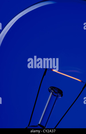 A light bulb on an electric blue background. - Stock Photo