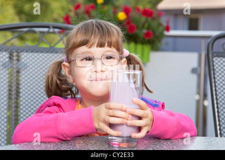 Little girl enjoying its milkshake - Stock Photo