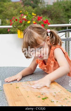 Girl blurs sauce on the cutting board - Stock Photo