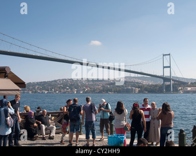 Sunday morning in Ortakoy Istanbul under the Bosphorus bridge, people relaxing enjoying and photographing life and - Stock Photo