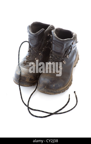dirty, muddy, old, used black walking boots or hiking boots isolated on a white background - Stock Photo