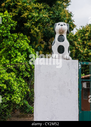A black and white spotted kitsch lawn art dog outside on a pedestal in Asunción Paraguay. - Stock Photo