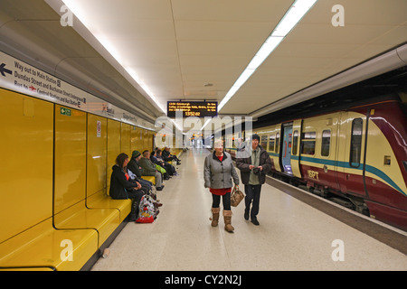 Passengers and a train on the Lower Level of Glasgow Queen Street railway station. Some are leaving the train, some - Stock Photo