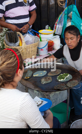 Woman preparing Blue Corn Tlayudas and Quesidillas on Comal at Jamaica Market in mexico City - Stock Photo