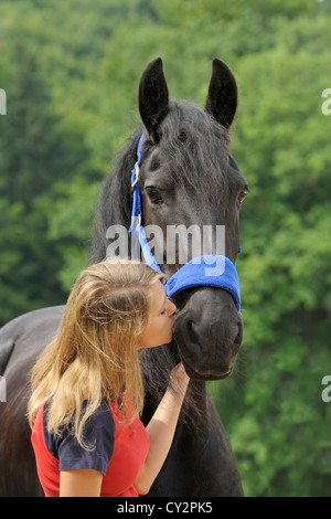 Young woman and a Friesian horse - Stock Photo
