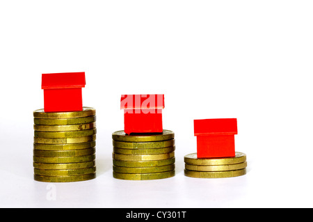 Plastic model houses balanced on top of stacks of coins.