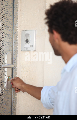 Man opening door with key - Stock Photo