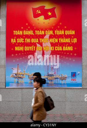 Couple Passing By A Propaganda Billboard Of The Communist Party, Hanoi, Vietnam - Stock Photo
