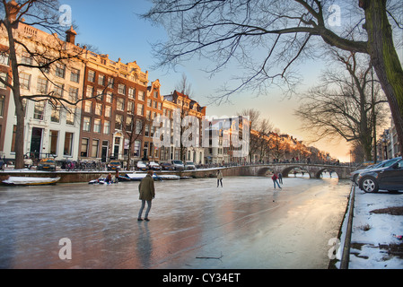 People skate on Amsterdam's frozen canals on a winter evening - Stock Photo