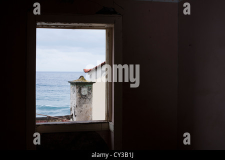 A view of the Atlantic Ocean from of the window of an abandoned house in the village of Jardim do Mar. - Stock Photo