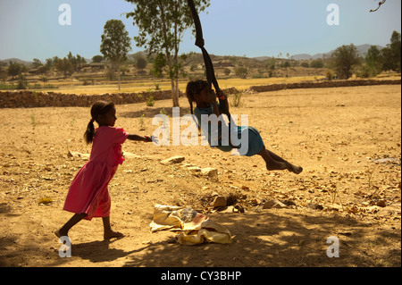Children playing on rustic swings made out of tire tubes and hanging from a tree branch in a field. - Stock Photo