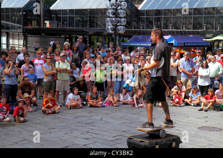 Boston Massachusetts Faneiul Hall Marketplace outside street performer audience man balancing watching - Stock Photo