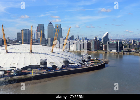 View of the O2 arena, with Canary Wharf and the Docklands behind, from the Emirates Air Line cable car, over the - Stock Photo