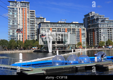 Aqua Balls attraction and the Emirates Airline cable cars leaving the Royal Docks terminus, in Newham, east London, - Stock Photo