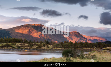 Mam na Gualain and Beinn na Caillich, lit by the evening sun. - Stock Photo