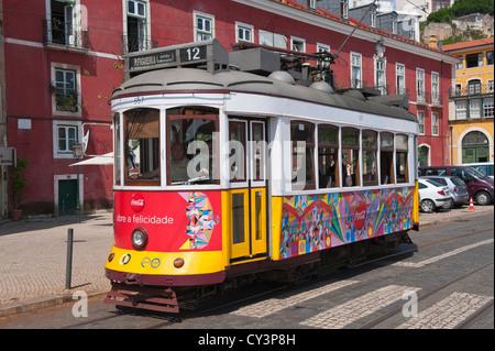 Tram in a street in Alfama district, Lisbon, Portugal - Stock Photo