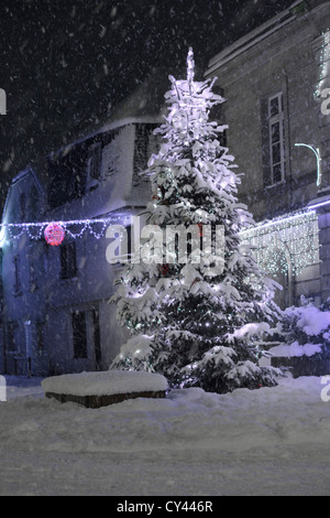 Europe, France, Brittany, Finistere (29), Carhaix Plouguer, Christmas tree in the snowy street by night - Stock Photo