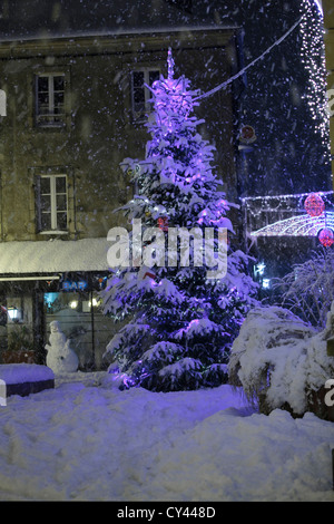 Europe, France, Brittany, Finistere (29), Carhaix Plouguer, Christmas tree and snowman in the snowy street by night - Stock Photo
