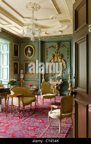 Louis XVI style settee and armchairs in green panelled drawing room with gilt framed portraits and red patterned - Stock Photo