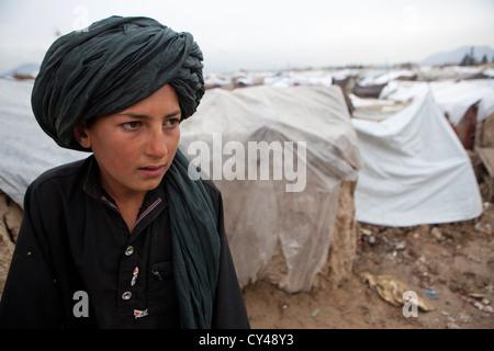 Afghan boy walking in a slum of kabul - Stock Photo