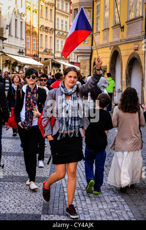 Czech tour guide waving her flag leading a group of tourists in Prague - Stock Photo