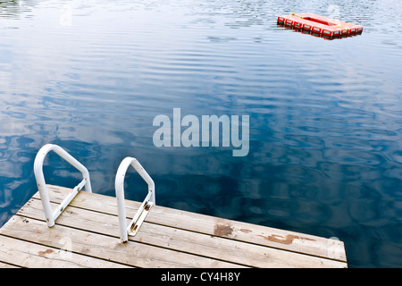 Dock and ladder on calm summer lake with diving platform in Ontario Canada - Stock Photo