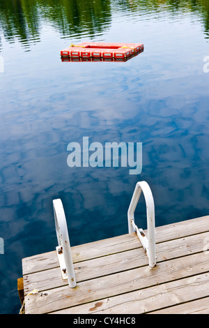 Dock and ladder on summer lake with diving platform in Ontario Canada - Stock Photo