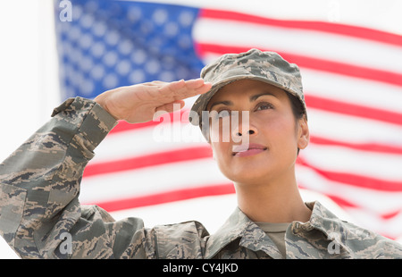 USA, New Jersey, Jersey City, Female army soldier saluting, American flag in background - Stock Photo