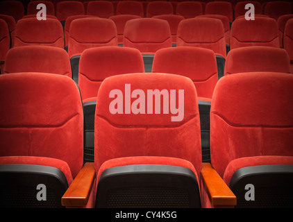 Red velvet armchairs in the empty auditorium - Stock Photo