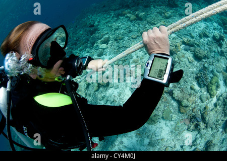 Diver ascends safety line, probably making safety stop after deep dive - Stock Photo