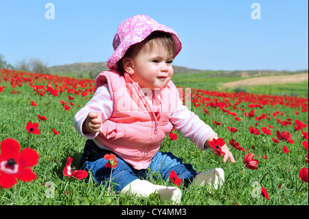 Baby girl sitting in a poppies field. - Stock Photo