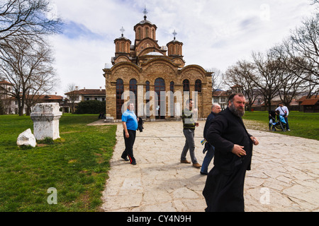 Serbian Orthodox priest and visitors at the UNESCO listed Gracanica monastery, Kosovo. - Stock Photo