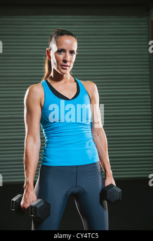 USA, California, Laguna Niguel, portrait of mid adult woman with free weights - Stock Photo