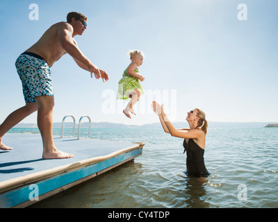 USA, Utah, Garden City, parents playing with their daughter (2-3) in lake - Stock Photo